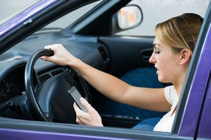 Young woman using cell phone while driving car | The Tragic Consequences of Distracted Driving