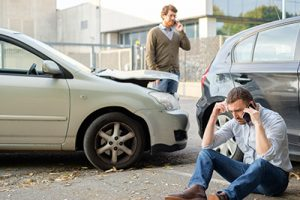 two men on cell phones after a fender bender | survive a minor car accident