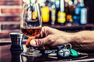 man holding glass of booze next to car keys on bar | Drunk Driving Accident Near Loveland