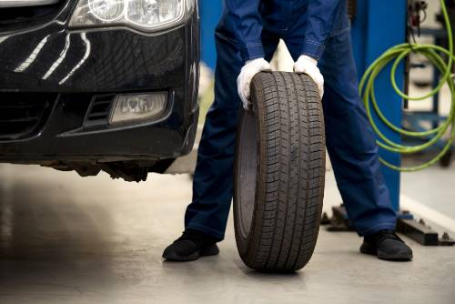car technician rolling a car's tire | tirewise